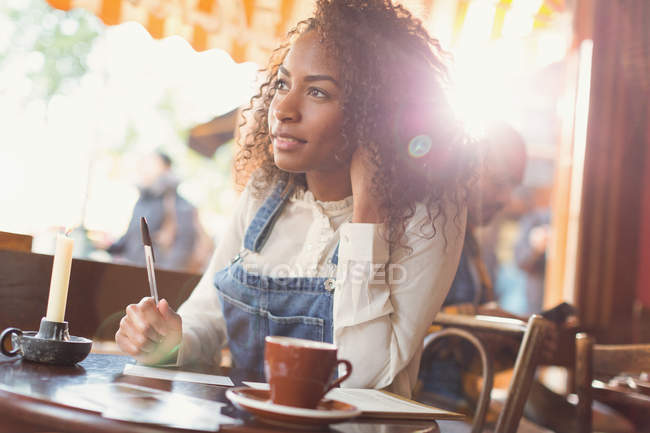 Pensive young woman writing postcard at cafe table — Stock Photo