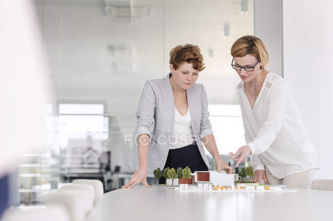 Female architects discussing model in conference room — Stock Photo