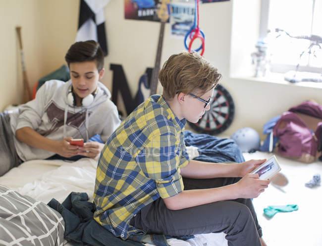 Due ragazzi adolescenti che utilizzano dispositivi digitali in camera — Foto stock