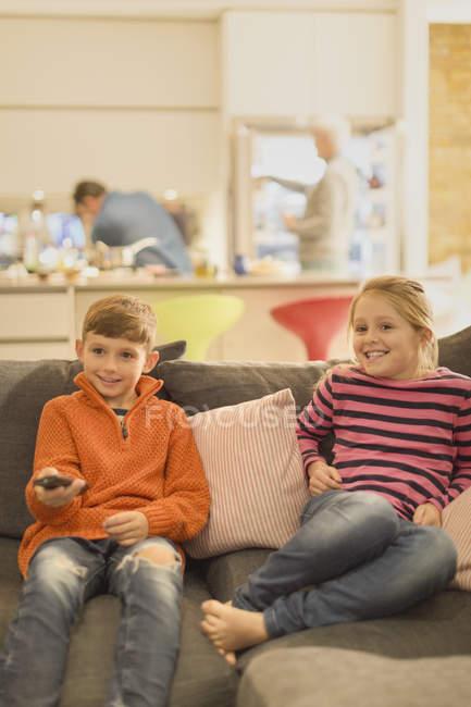 Frère et sœur, regarder la télévision sur le canapé du salon — Photo de stock