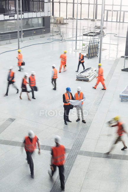 Engineers reviewing blueprints at construction site — Stock Photo