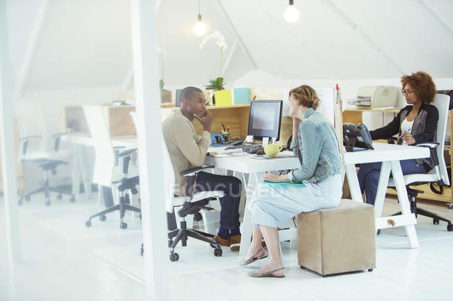 Office workers talking at desk in modern office — Stock Photo