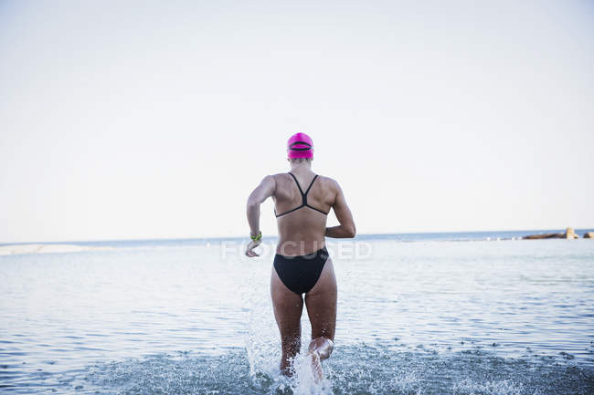 Rear view of Female active swimmers running at ocean outdoors — Stock Photo