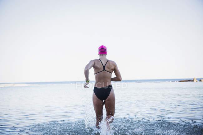 Vista traseira do femininos ativos nadadores executando no oceano ao ar livre — Fotografia de Stock