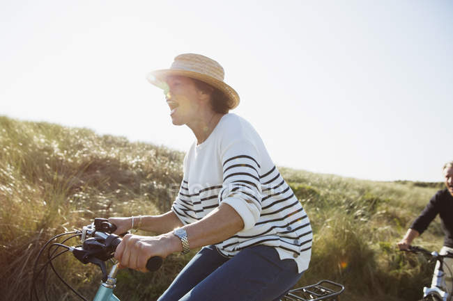 Playful mature woman riding bicycle on sunny beach grass path — Stock Photo