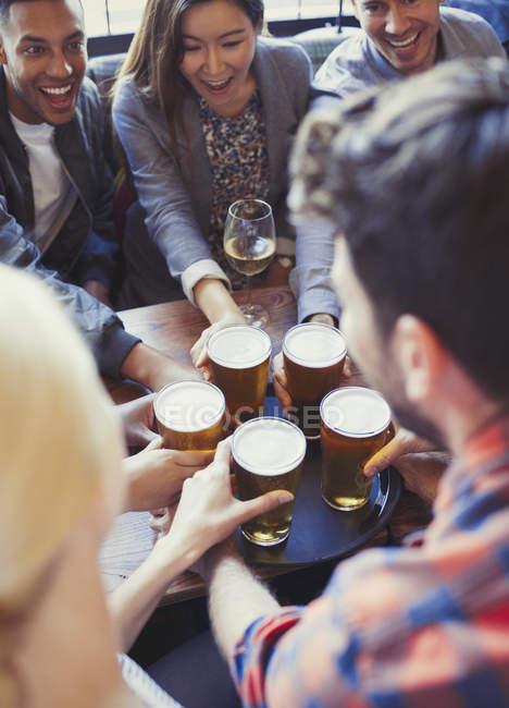 Бармен, служачи пива на лоток для друзів в м. бар — стокове фото