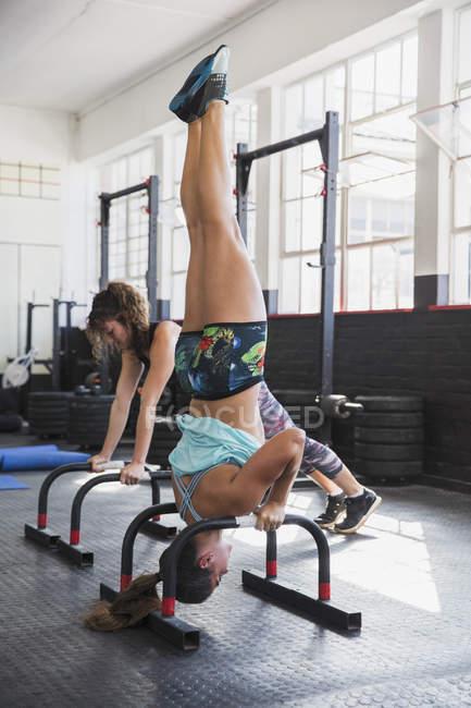 Молода жінка робить стенд плечі вгору вниз в тренажерний зал — стокове фото