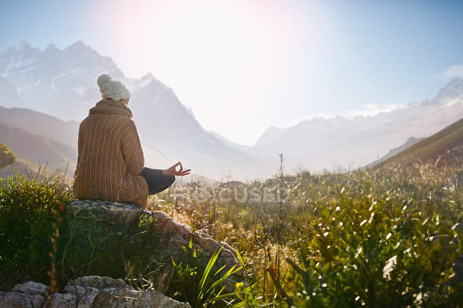 Молодая женщина медитирует на скале в солнечной, отдаленной долине — стоковое фото
