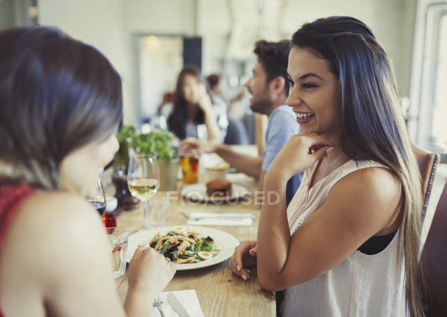 Smiling women friends talking and eating at restaurant table — Stock Photo