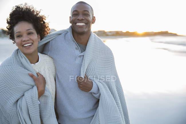 Portrait of couple wrapped in blanket on beach — Stock Photo