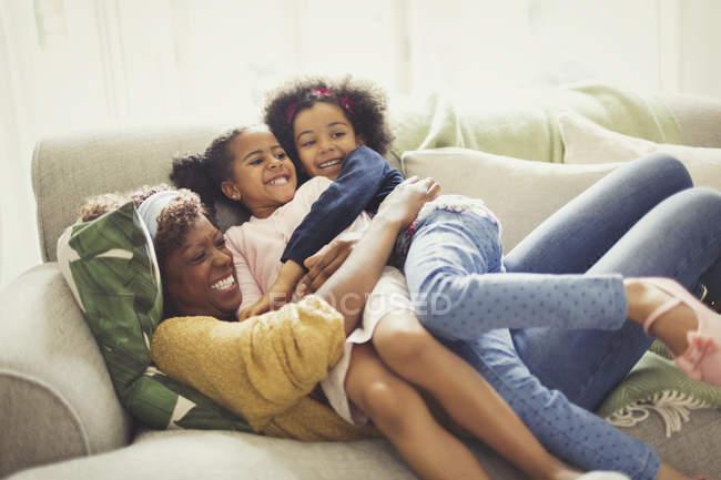 Mãe e filhas brincalhão abraçando no sofá — Fotografia de Stock