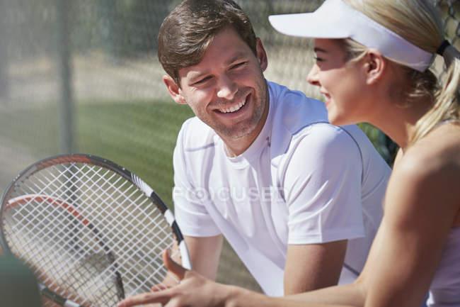 ec88ff36aa4 Sonriendo de tenistas masculinos y femeninos descansando y hablando con  raquetas de tenis en exteriores soleados — al aire libre