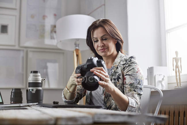 Female photographer using digital camera in office — Stock Photo