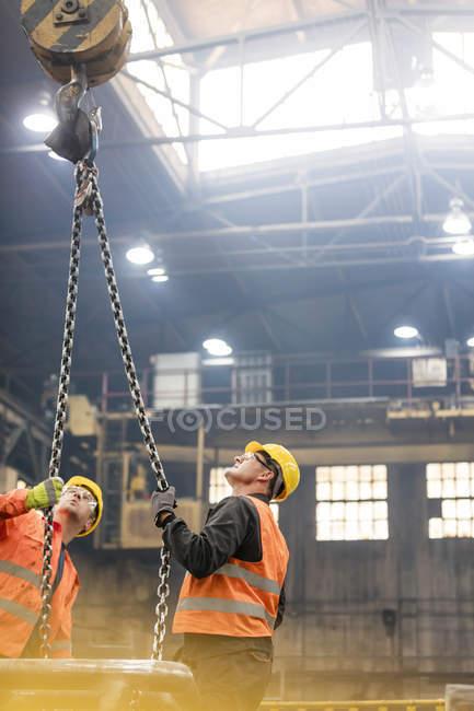 Сталеві робітників, дивлячись на кран ланцюг заводі — стокове фото