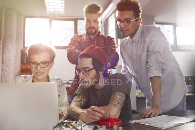 Four young designers working at laptop — Stock Photo