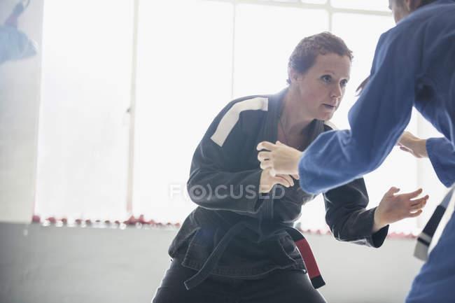 Визначається, жорстка жінка практикуючих дзюдо в тренажерний зал — стокове фото