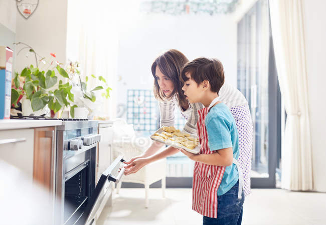 Mother and son baking, placing cookies in oven in kitchen — Stock Photo