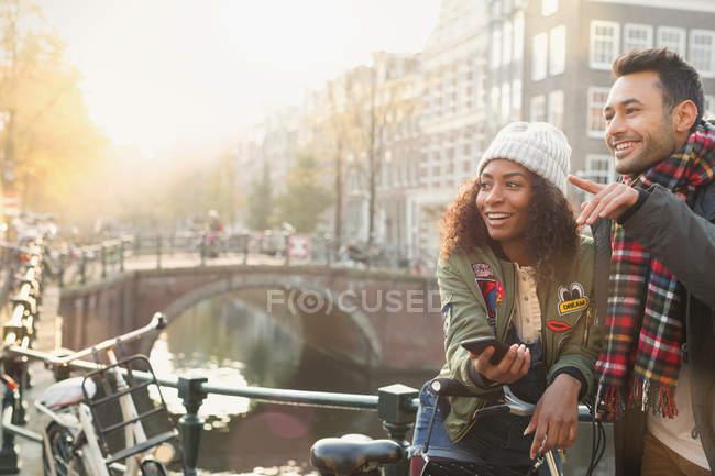 Jeune couple avec vélos sur pont urbain au-dessus du canal, Amsterdam — Photo de stock