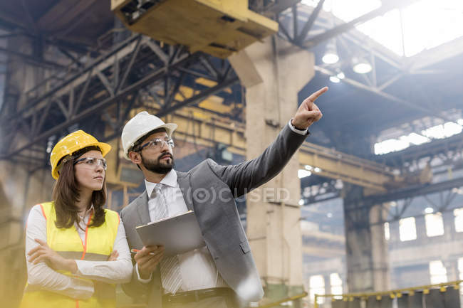 Manager and female steel worker talking looking away in factory — Stock Photo