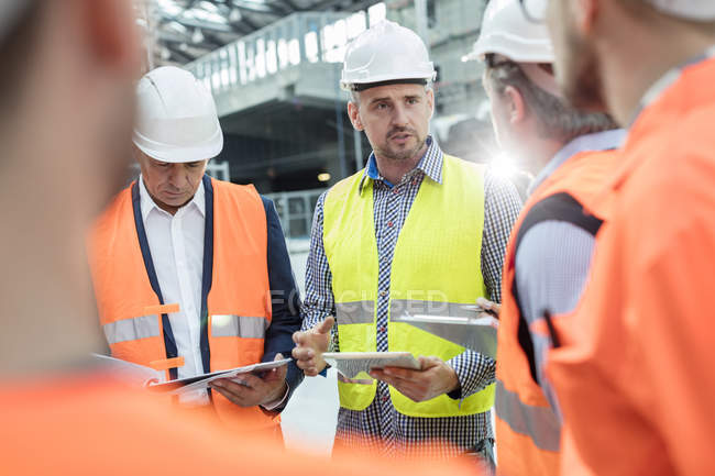 Male foreman, engineers and construction workers meeting at construction site — Stock Photo