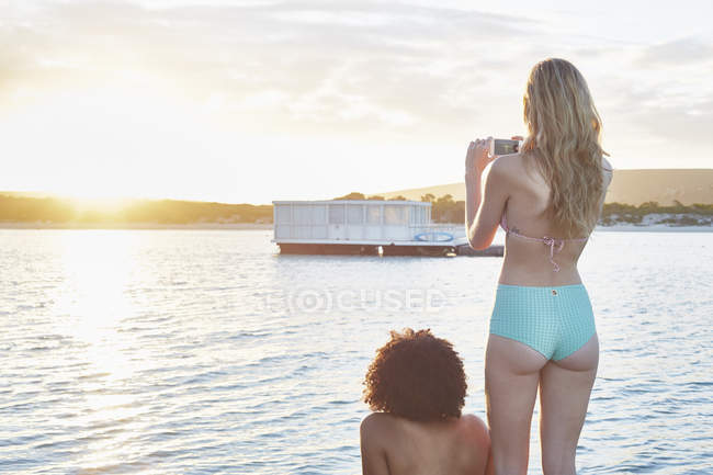 Young woman in bikini photographing houseboat on sunny summer ocean — Stock Photo