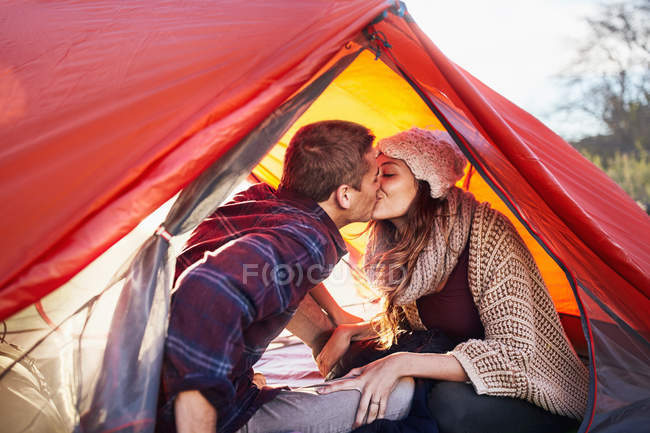 Young couple camping, kissing inside tent — Stock Photo
