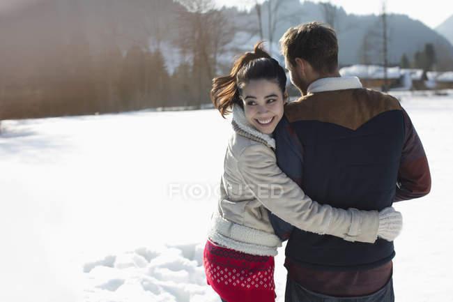 Счастливая пара, идущая по снегу — стоковое фото