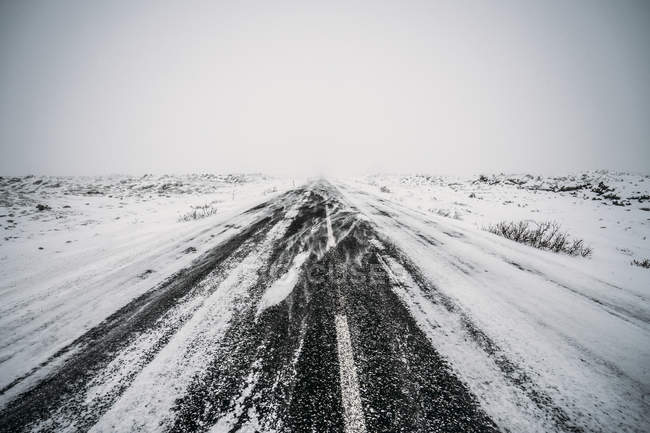 Diminishing perspective remote snow covered road — Stock Photo