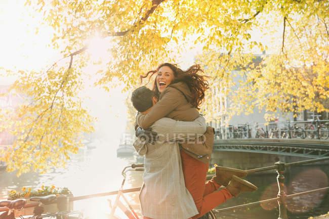 Begeistertes paar, das sich am sonnigen herbstkanal in amsterdam umarmt — Stockfoto