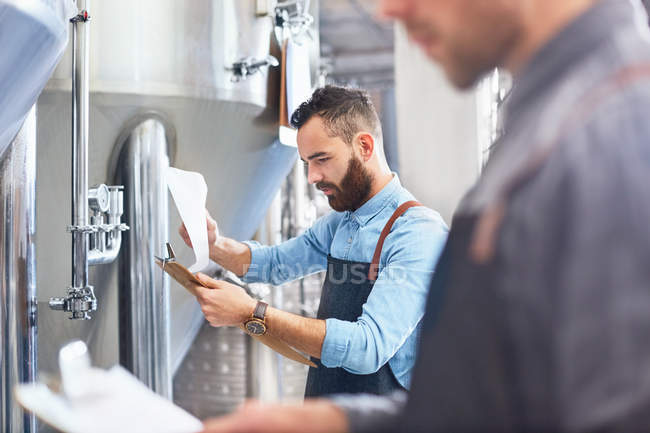 Male brewer with clipboard at vat in brewery — Stock Photo