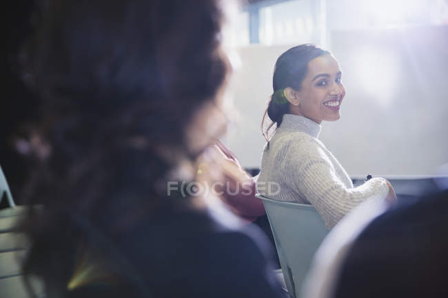 Smiling businesswoman turning, looking back in conference audience — Stock Photo