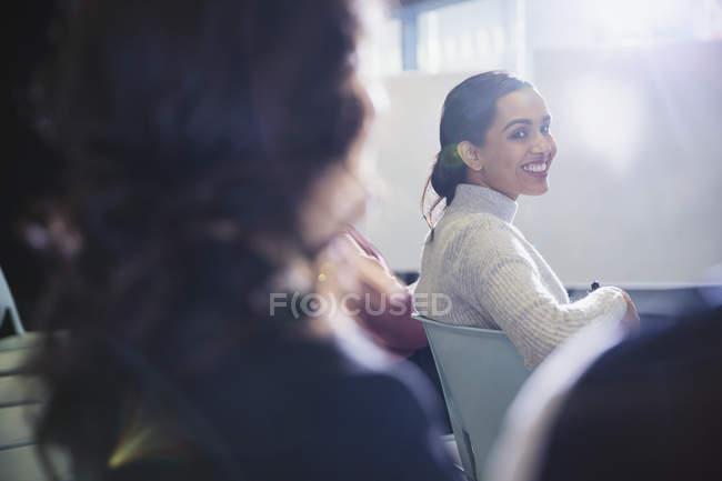 Femme d'affaires souriante tournant, regardant en arrière dans le public de la conférence — Photo de stock