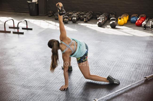 Junge Frau, dehnen, mit Wasserkocher Glocke im Fitness-Studio — Stockfoto