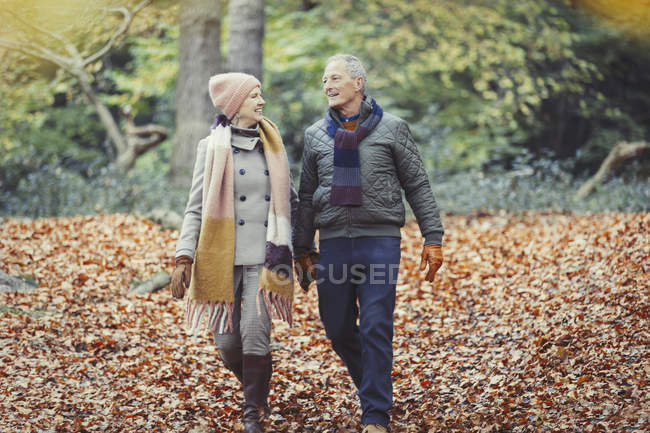 Senior couple walking in autumn leaves in park — Stock Photo