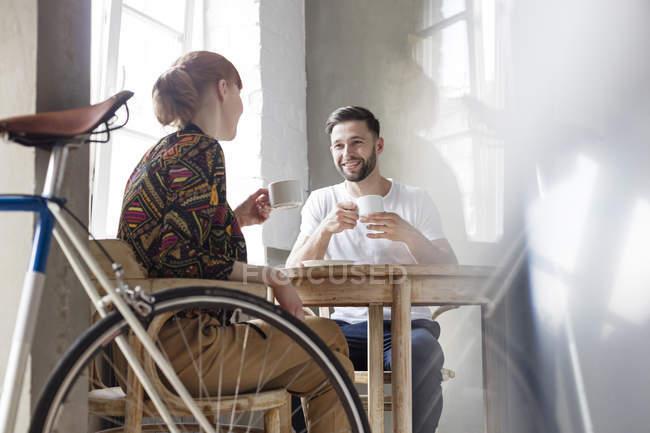 Coppia parlando e bevendo caffè a tavola — Foto stock
