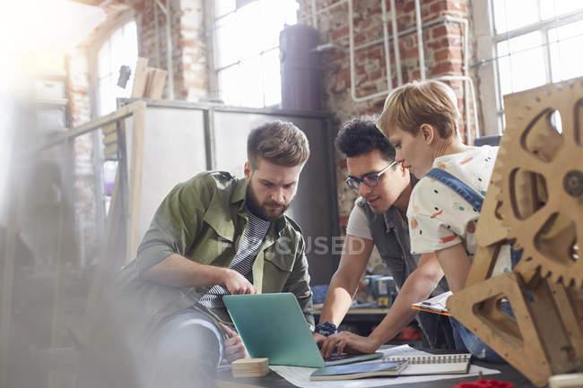 Giovani designer che lavorano al computer portatile in laboratorio — Foto stock