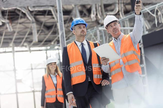 Empresário e engenheiro conversando no canteiro de obras — Fotografia de Stock