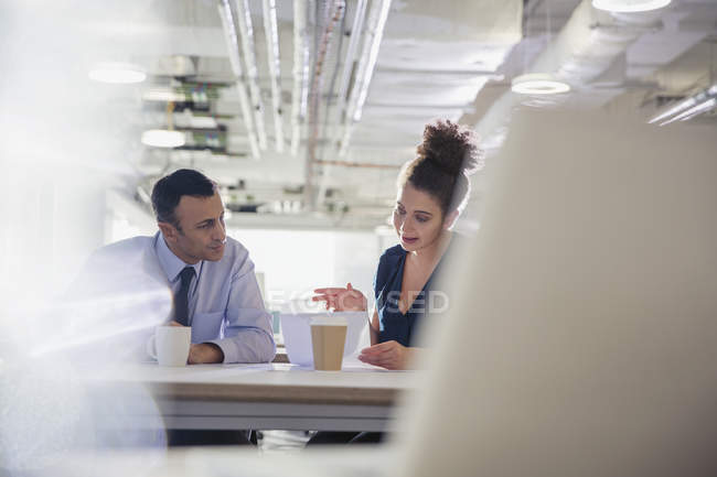Businessman and businesswoman discussing paperwork in office meeting — Stock Photo