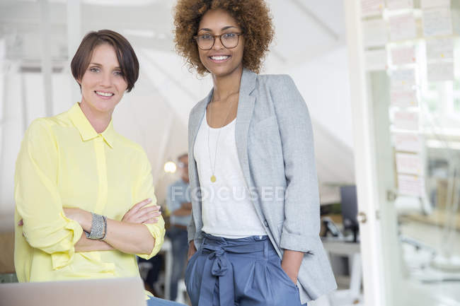 Portrait of female colleagues smiling in office — Stock Photo
