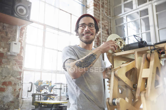 Male designer with tattoos working on prototype in workshop — Stock Photo