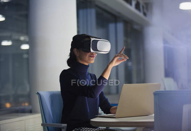 Businesswoman using virtual reality simulator at laptop in office — Stock Photo