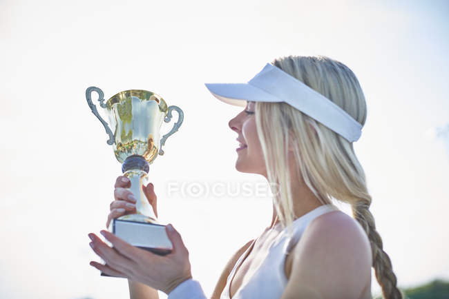 Блондинка юная теннисистка в козырьке, обладающая трофеем чемпионата — стоковое фото