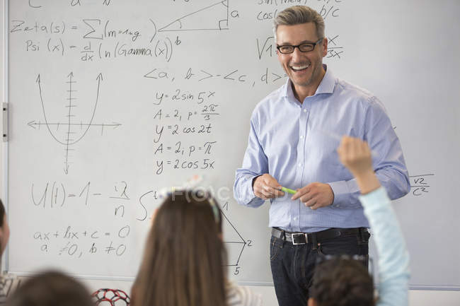 Усміхаючись чоловічого наука вчителя провідних урок на дошці в класі — стокове фото