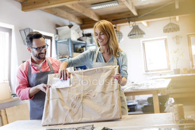 Smiling artists wrapping stained glass project in studio — Stock Photo
