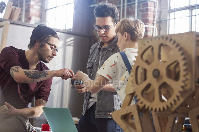 Designers examining and discussing prototype in workshop — Stock Photo