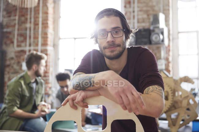 Портрет впевнено чоловічого дизайнер з татуюваннями, спираючись на прототип в майстерні — стокове фото