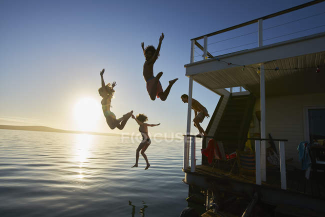 Young adult friends jumping off summer houseboat into sunset ocean — Stock Photo