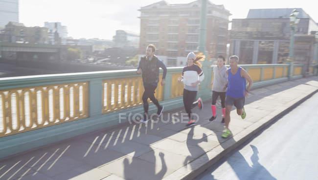 Runners running on sunny urban bridge — Stock Photo