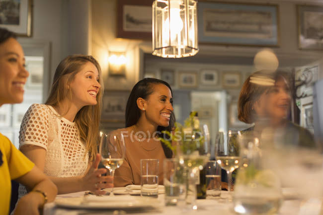 Smiling women friends looking away dining and drinking white wine at restaurant table — Stock Photo