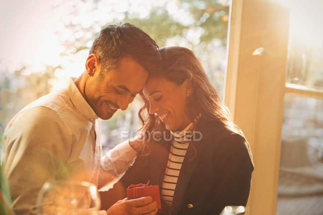 Ласкава, романтичні бойфренд одержання подарунку подругою в Сонячний кафе — стокове фото